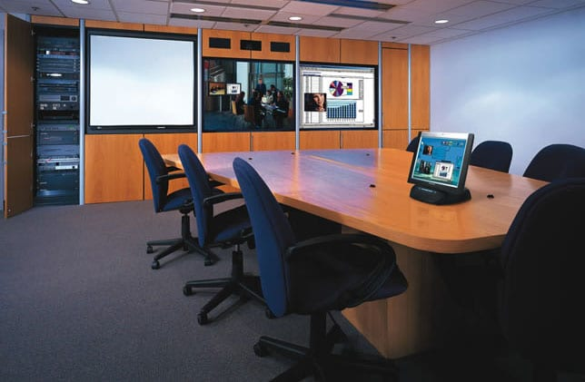 Conference room with  a wall of TV monitors and a cabinet for A/V Components