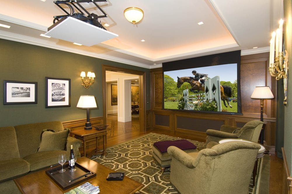 Pop-down ceiling projector and a roll up projection screen transforms a family room into a home theater