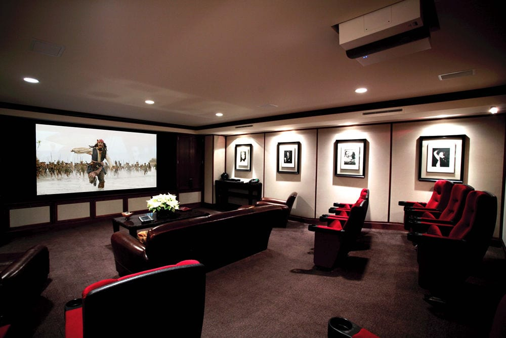 home theater room with a mix of leather couches and theater-style seating