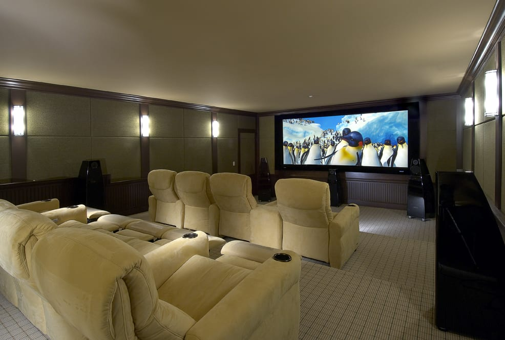Home Theater Room With Tan Recliner Seating A Large Flatscreen Tv And Subwoofers