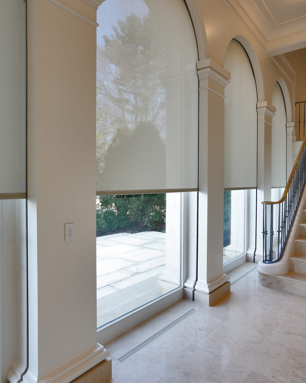 hallway with tall arched windows that have motorized shades